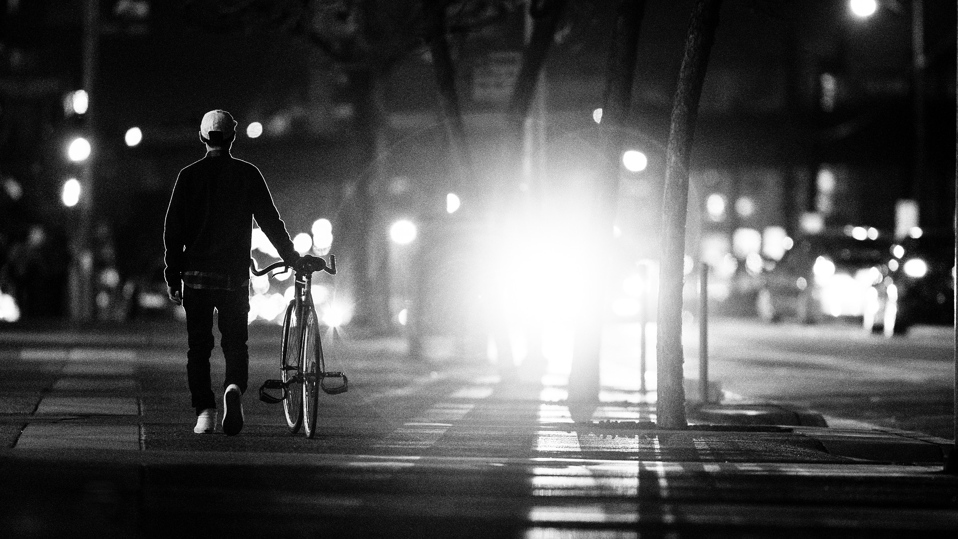 Person riding bike down street at night