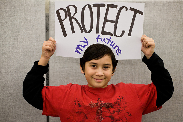Child holding sign that says