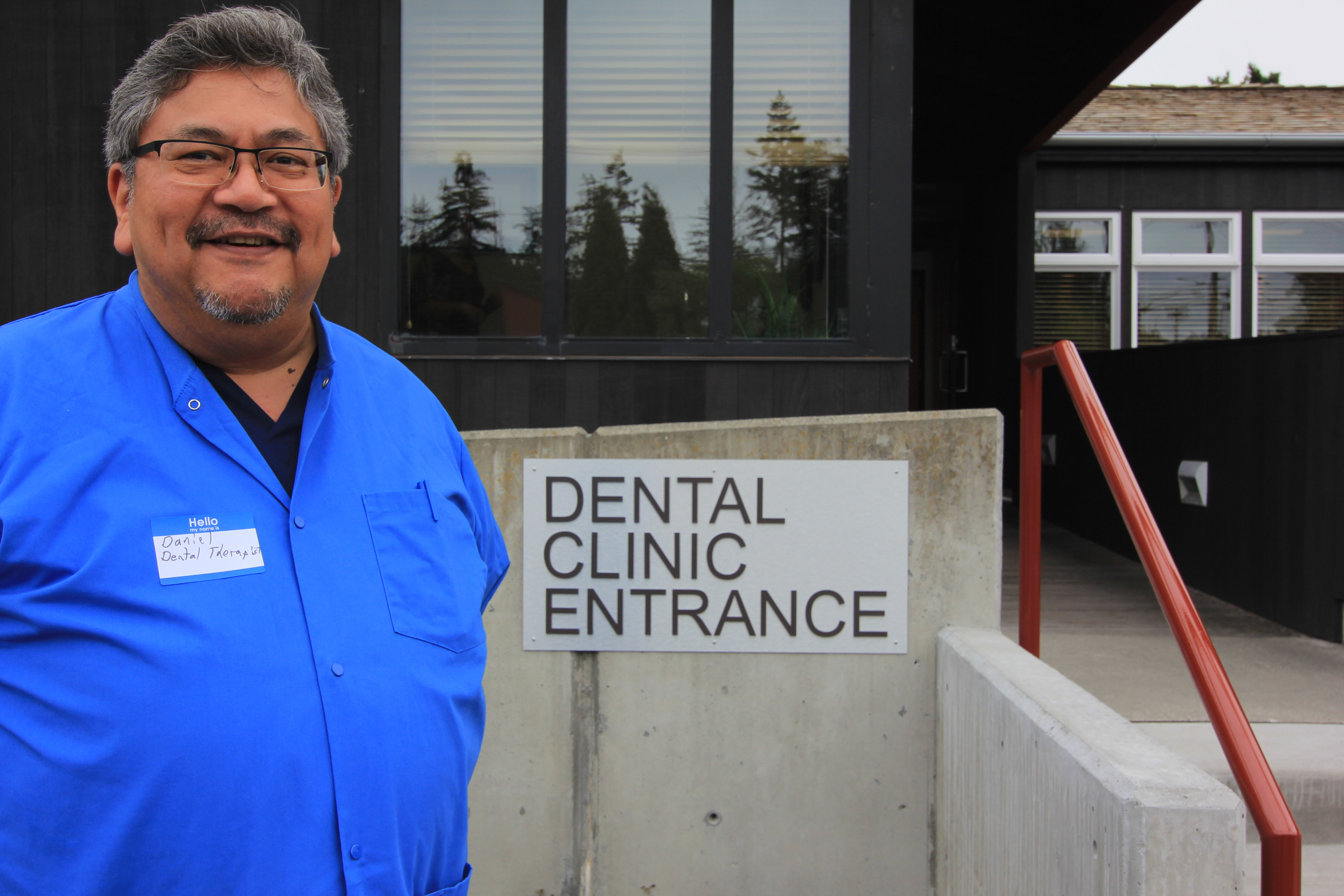Dental Therapist Daniel Kennedy in front of the Dental Clinic entrance. Daniel has been practicing there since 2016.